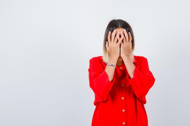 Portret van een mooie dame die haar gezicht bedekt met handen in een rode blouse en beschaamd vooraanzicht kijkt