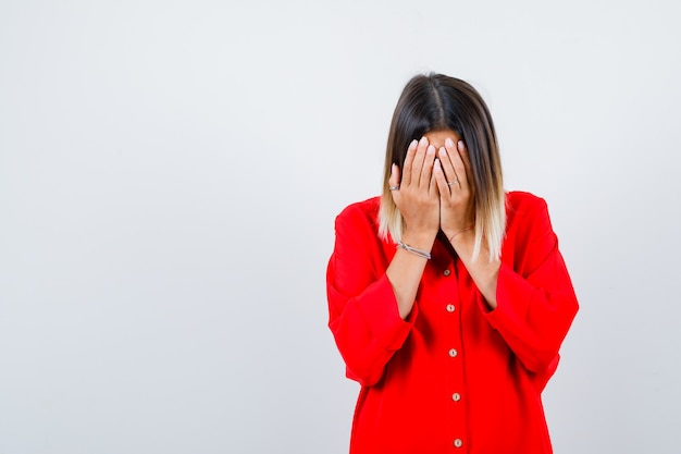 Portret van een mooie dame die haar gezicht bedekt met handen in een rode blouse en er depressief uitziet