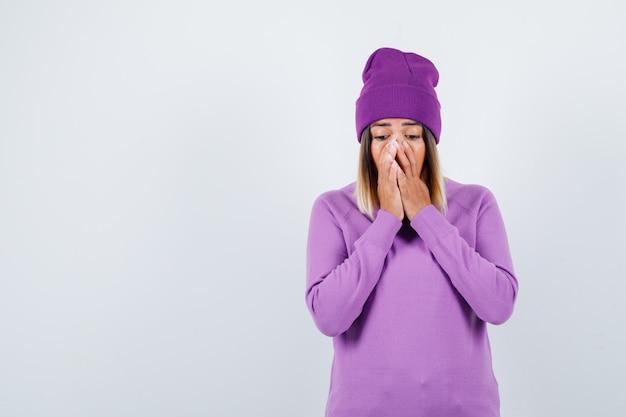Portret van een mooie dame die haar handen op het gezicht houdt in trui, muts en geschokt vooraanzicht kijkt