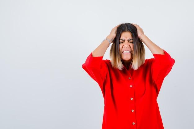 Portret van een mooie dame die handen op het hoofd houdt in een rode blouse en er geïrriteerd vooraanzicht uitziet