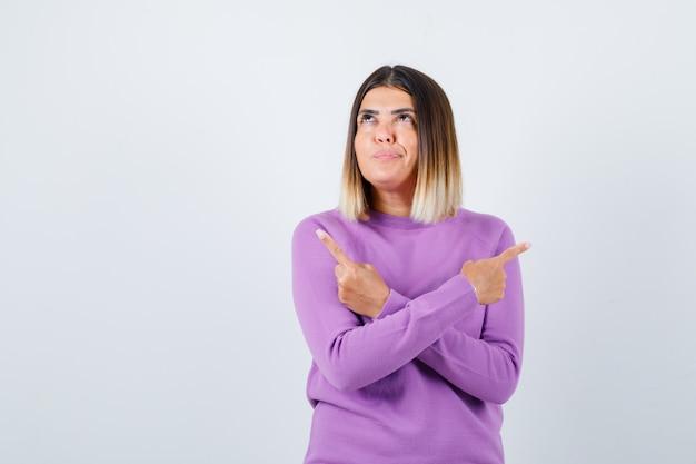 Portret van een mooie dame die naar de linker- en rechterkant in de trui wijst en er vrolijk vooraanzicht uitziet