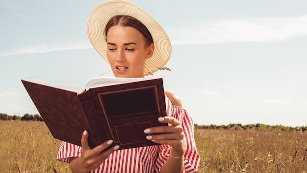Portret van een mooie dame. leest een boek in het veld. bereid je voor op toelating tot de universiteit.