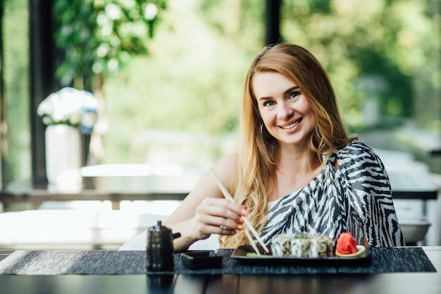 Portret van een mooie dame van middelbare leeftijd zit in het café op het zomerterras met sushirollen.