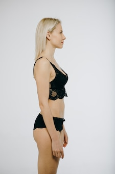 Portret van een mooie donkerbruine vrouw in zwarte bikini die op wit wordt geïsoleerd