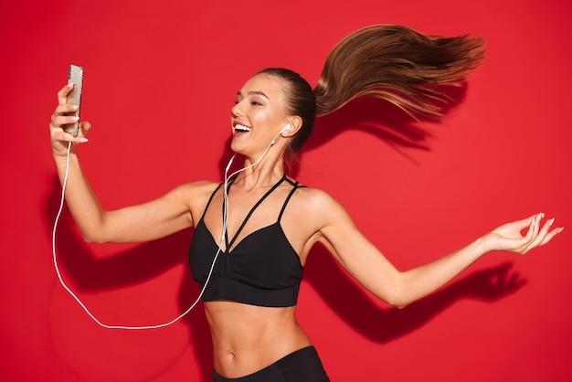 Portret van een mooie fit jonge sportvrouw springen, luisteren naar muziek met koptelefoon, mobiele telefoon te houden