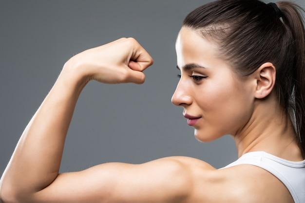 Portret van een mooie fitness vrouw die haar biceps toont die op grijze achtergrond wordt geïsoleerd