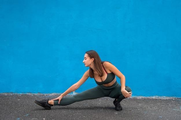 Portret van een mooie fitnessvrouw in groene sportkleding. sport voor een gezonde levensstijl