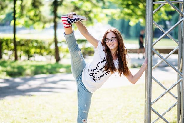 Portret van een mooie flexibele vrouw die spleet in het park op een zonnige dag doet