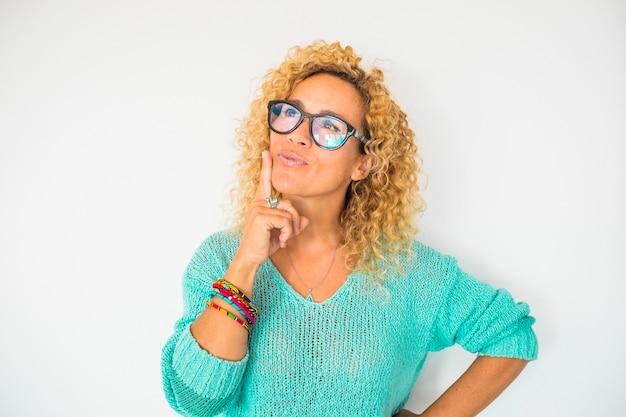 Portret van een mooie gekrulde vrouw die denkt en droomt - close-up van dromerige mensen met een bril en een blauw shirt met een witte achtergrond