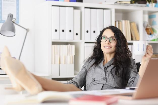Portret van een mooie gelukkig lachende jonge vrouw die aan de tafel van het kantoor aan huis zit met een kopje koffie