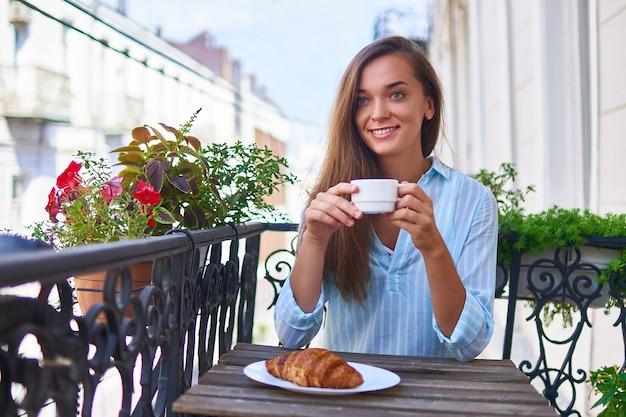 Portret van een mooie gelukkig schattige vrolijke lachende romantische vrouw met een aromatische koffiekopje in handen en een bord met vers gebakken croissant op de tafel in de ochtend op een balkon
