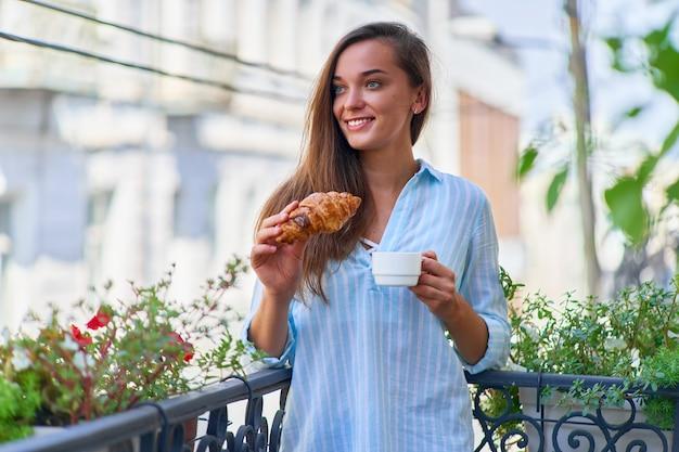 Portret van een mooie gelukkig schattige vrolijke lachende romantische vrouw met koffiekopje en vers gebakken croissant voor frans ontbijt in de ochtend op een balkon