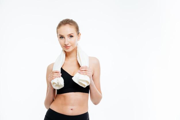 Portret van een mooie, gelukkige jonge sportvrouw die met een witte handdoek om haar nek staat