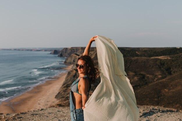 Portret van een mooie gelukkige jonge vrouw die met een zakdoek en de wind op de bovenkant van een heuvel speelt. zomertijd. levensstijl