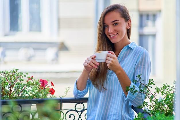 Portret van een mooie gelukkige leuke vrolijke glimlachende romantische vrouw met een aromatische koffiekop in handen in de ochtend op een balkon