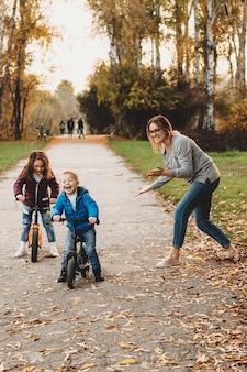 Portret van een mooie gelukkige moeder buiten spelen met haar kinderen terwijl zoon gaat lachen op de fiets.