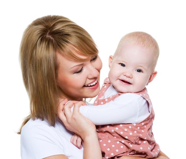 Portret van een mooie gelukkige moeder met baby die op wit wordt geïsoleerd