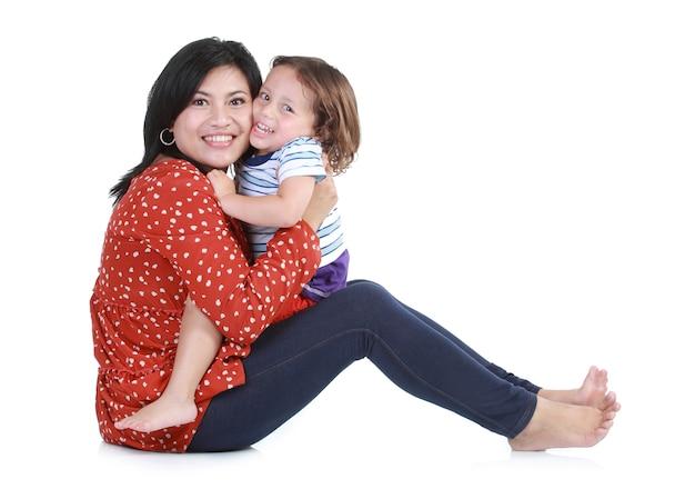Portret van een mooie gelukkige moeder met glimlachende jongen die op wit wordt geïsoleerd