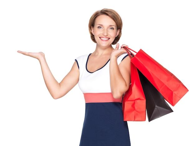Portret van een mooie gelukkige vrouw met presentatiegebaar en boodschappentassen over witte muur