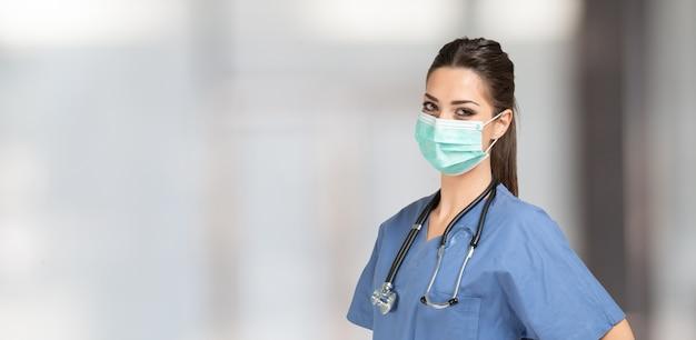 Portret van een mooie gemaskerde verpleegster tijdens coronavirus pandemie