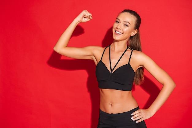 Portret van een mooie geschikte jonge sportvrouw die zich, biceps buigt