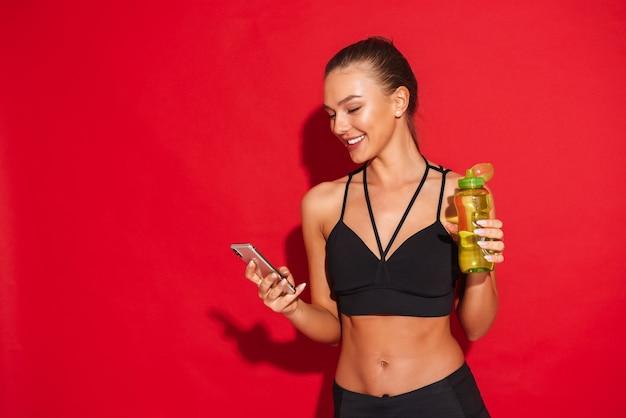 Portret van een mooie geschikte jonge sportvrouw die zich, mobiele telefoon vasthoudt, waterfles toont