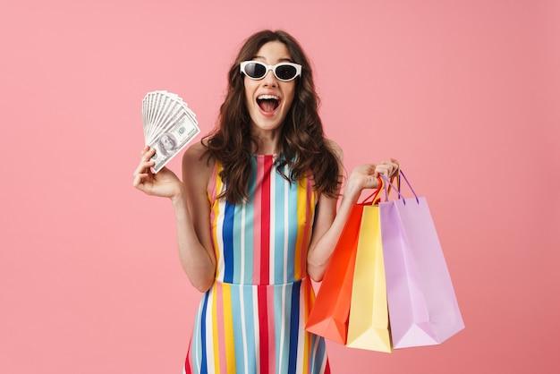 Portret van een mooie geschokte verraste positieve jonge leuke vrouw die zich over een roze muur geïsoleerd stelt, met boodschappentassen en geld