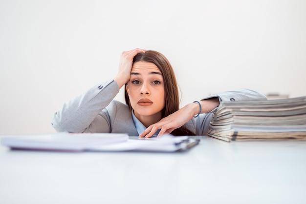 Portret van een mooie gestresst zakenvrouw op bureau met een bureau met een stapel papierwerk.