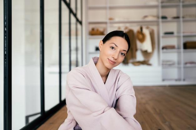 Portret van een mooie gezonde vrouw in badjas poseren binnenshuis