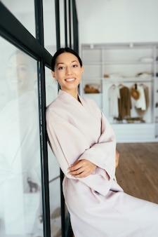 Portret van een mooie gezonde vrouw in een badjas die binnenshuis voor de camera poseert