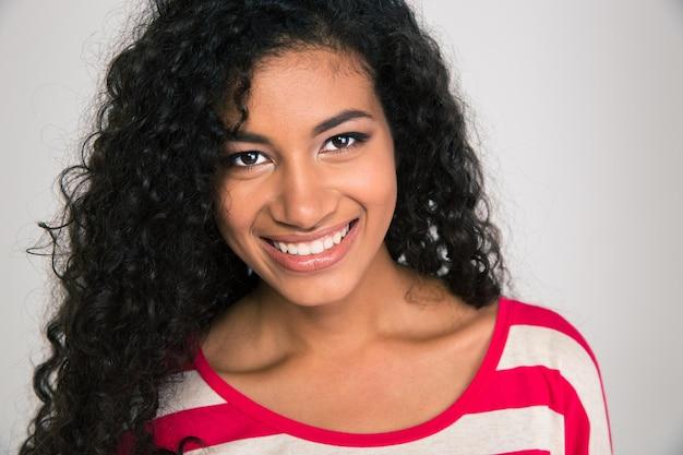 Portret van een mooie glimlachende afro-amerikaanse vrouw die camera bekijkt die op een witte muur wordt geïsoleerd