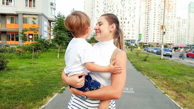 Portret van een mooie glimlachende jonge moeder die haar peuterzoon vasthoudt en op straat loopt