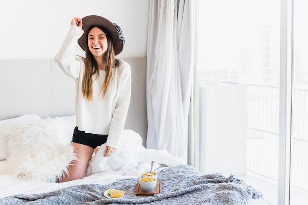Portret van een mooie glimlachende jonge vrouw op bed met ontbijt