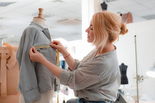Portret van een mooie glimlachende naaister met een meetlint naast een mannequin in merkkleding in een kleermakersatelier
