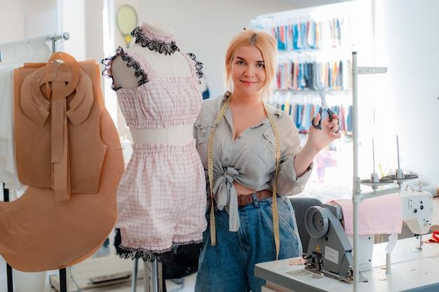Portret van een mooie glimlachende naaister met een meetlint naast een mannequin in merkkleding