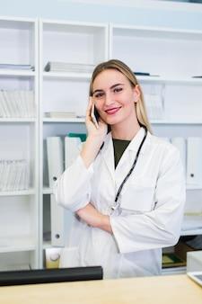 Portret van een mooie glimlachende verpleegster bij het bureaustation tijdens het telefoneren