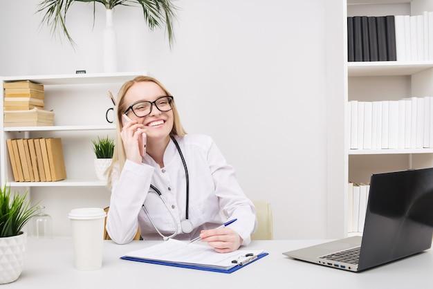 Portret van een mooie glimlachende vrouw arts tijdens het praten op de smartphone en een medische informatie invullen