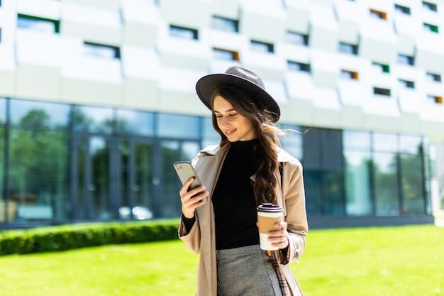 Portret van een mooie glimlachende vrouw die mobiele telefoon met behulp van terwijl koffiekop op een stadsstraat wordt gehouden