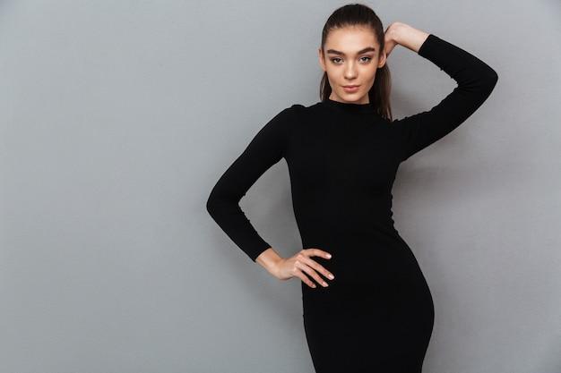 Portret van een mooie glimlachende vrouw in zwarte jurk poseren