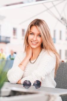 Portret van een mooie glimlachende vrouw met ronde zonnebril op tafel