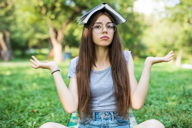 Portret van een mooie grappige schattige gelukkige jonge dame studente zitten in park buiten op groen gras dragen bril met voorbeeldenboek album boven haar hoofd.