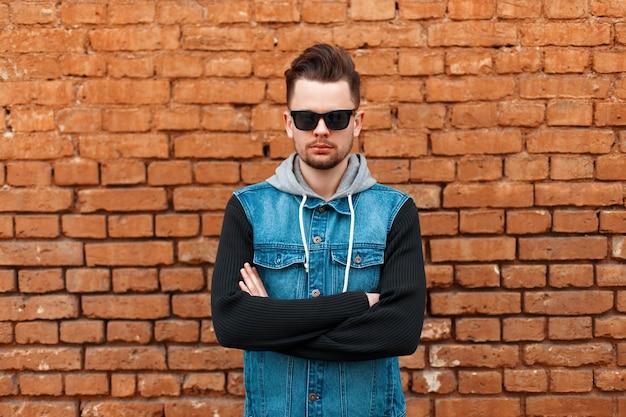 Portret van een mooie hipster man in een denim vest in de buurt van een bakstenen muur
