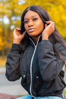 Portret van een mooie jonge afro-amerikaanse vrouw met een zwarte modieuze jas in de natuur op een achtergrond van geel herfstgebladerte