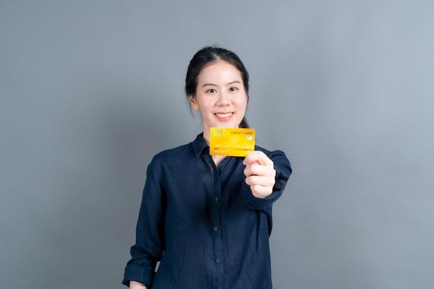 Portret van een mooie jonge aziatische vrouw die creditcard met exemplaarruimte op grijze muur toont