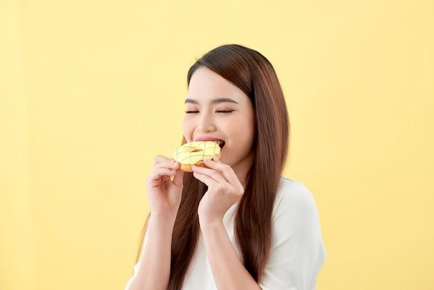 Portret van een mooie jonge aziatische vrouw die donuts eet die over gele achtergrond worden geïsoleerd