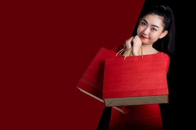 Portret van een mooie jonge aziatische vrouw die een rode kleding draagt die boodschappentas houdt