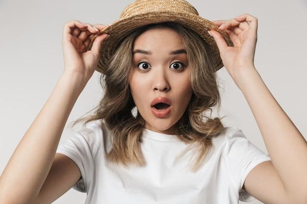 Portret van een mooie jonge aziatische vrouw die geïsoleerd staat over een witte muur, een zomerhoed draagt, poserend