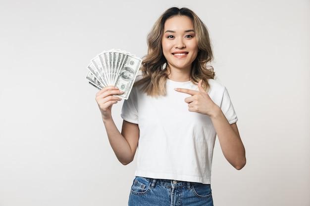 Portret van een mooie jonge aziatische vrouw die geïsoleerd staat over een witte muur en geldbankbiljetten toont
