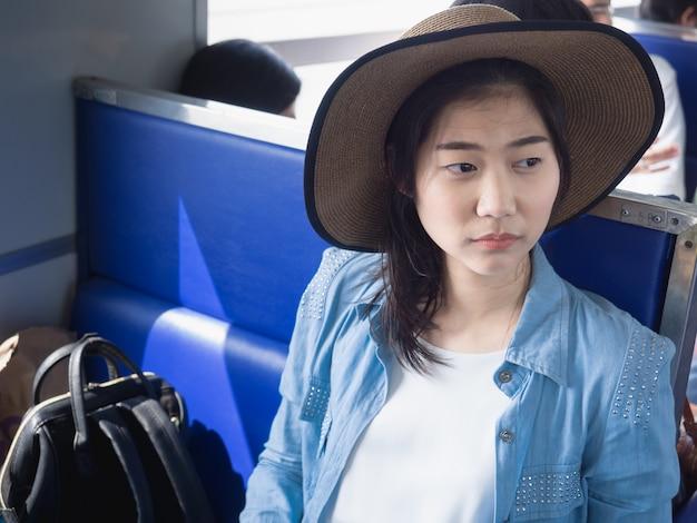 Portret van een mooie jonge aziatische vrouw die hoed aan de gang draagt