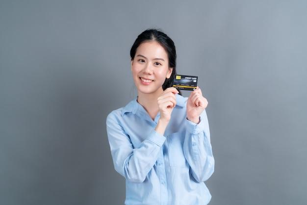 Portret van een mooie jonge aziatische vrouw in blauw shirt met creditcard met kopie ruimte op grijze achtergrond